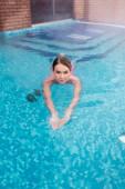 mladá žena koupání ve venkovním bazénu s modrou vodou