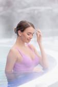 pára v blízkosti usmívající se mladá žena koupání v venkovní horké jarní bazén