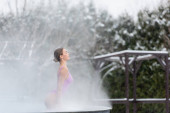 side view of woman with closed eyes bathing in outdoor hot spring pool