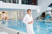 glückliche junge Frau im weißen Bademantel, die in der Nähe des Pools im Wellnesszentrum steht