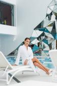 teljes hossza fiatal nő fürdőköpenyben ül a fedélzeten szék spa center