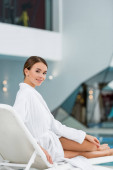 happy young woman in bathrobe resting on deck chair in spa center