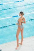 Zadní pohled na mladou ženu v plavkách stojící u bazénu