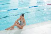 Sexy žena sedí v blízkosti bazénu v lázeňském centru