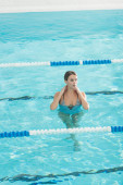 Mladá žena s rukama u krku dívá pryč v bazénu