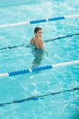 Zadní pohled mladé ženy při pohledu na kameru v bazénu