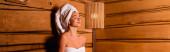 Příjemná žena v ručnících sedící v sauně, banner