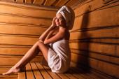 žena se usmívá na kameru na dřevěné sedačce v sauně