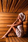 Boční pohled ženy relaxující v sauně lázeňského centra