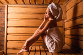 Boční pohled na veselou ženu v ručnících sedící v sauně
