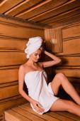 Junge Frau in Handtücher gehüllt auf Sitz in Holzsauna