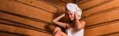 Lächelnde Frau fixiert Handtuch auf dem Kopf in Sauna, Banner