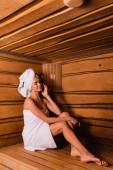 Zufriedene Frau mit geschlossenen Augen entspannt in Holzsauna