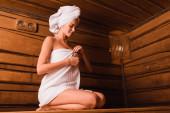 Hübsche Frau fixiert Handtuch in hölzerner Sauna des Kurzentrums