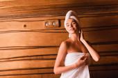 Radostná žena se zavřenýma očima stojící v dřevěné sauně