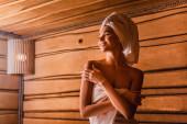 Glückliche Frau entspannt sich in Holzsauna vor verschwommenem Hintergrund