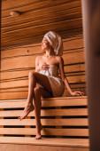 Veselá bosá žena v ručnících sedící v sauně