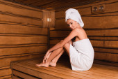 Žena v bílých ručnících při pohledu na kameru na dřevěné sedačce v sauně