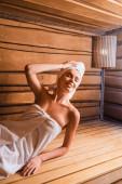 Fröhliche Frau mit Hand nahe Kopfstütze auf Sitz in Sauna