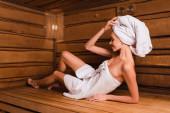 Šťastná žena ležící na sedadle v moderní sauně
