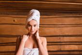 Junge Frau schaut in die Kamera, während sie sich in der Sauna entspannt