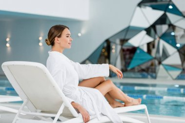 Full length of pleased young woman in white bathrobe resting on deck chair near pool stock vector