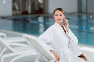 Young woman in white bathrobe looking away while resting on deck chair near pool stock vector