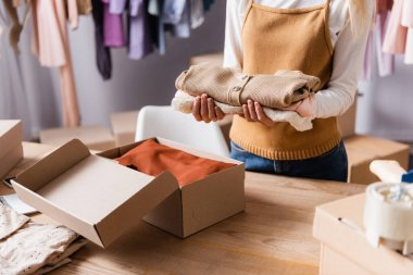 Cropped view of showroom owner holding clothes near carton boxes in showroom stock vector