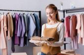 šťastný showroom majitel drží oblečení v blízkosti ramínka na rozmazaném pozadí