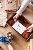 Teilansicht der Verkäuferkarte mit Dankeschön-Schriftzug in der Nähe der Box mit Kleidung im Showroom
