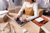 Teilansicht einer Geschäftsfrau, die auf Laptop neben Kleidung und Kartons im Showroom tippt