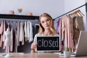 rozrušená podnikatelka držící desku s uzavřeným nápisem v showroomu, rozmazané popředí