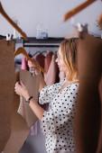 mladý oděvní návrhář držící šablony v ateliéru na rozmazaném popředí