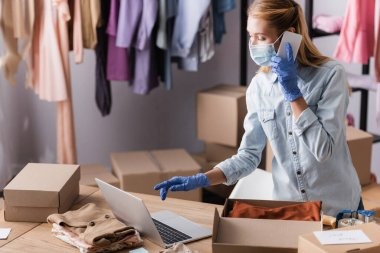 Seller in medical mask, accepting order on mobile phone while working near laptop and boxes in showroom stock vector