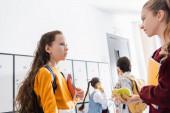 Mädchen mit Äpfeln und Heften unterhalten sich auf dem Schulflur