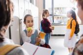 Happy child holding ripe apple and notebook while looking at schoolkids on blurred foreground