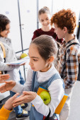 Schoolgirl with apple and notebook playing patty cake game with friend in school