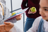 Notebook és alma a kezében iskolás fiú közelében barátok elmosódott előtérben