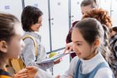 Iskolásfiú kezében alma és notebook közel barátja mutogatott ujjal az iskola előcsarnokában
