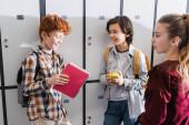 Vidám gyerekek jegyzetfüzettel, almával és hátizsákkal az iskolai szekrények közelében.
