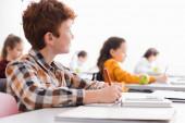 Schoolboy írás notebook közelében laptop elmosódott előtérben osztályteremben