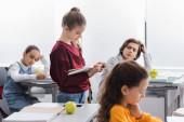 Žák čtení knihy v blízkosti jablko, smartphone a spolužáci na rozmazaném pozadí