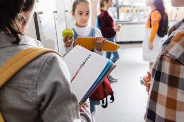 Open notebook in hand of schoolboy near friends on blurred background in school stock vector