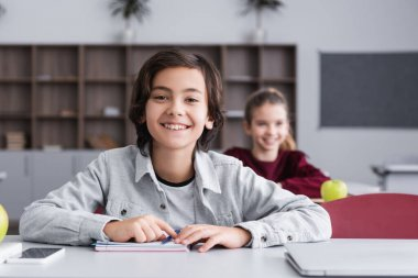 Smiling child looking at camera near devices and notebook on desk in classroom stock vector