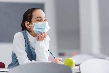 Schoolgirl in protective mask holding pen near apple on desk in school stock vector