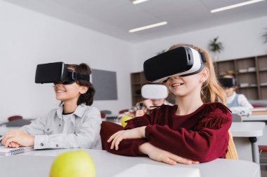 Happy schoolchildren gaming in vr headsets during lesson, blurred background stock vector