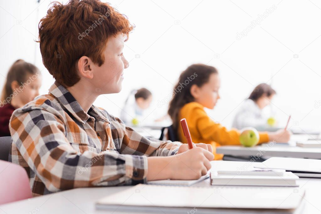 Schoolboy writing on notebook near laptop on blurred foreground in classroom stock vector