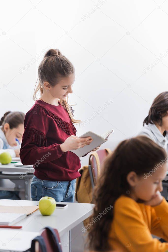 Cheerful schoolgirl reading book near classmates in classroom stock vector