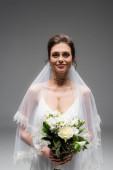 Lächelnde Braut in Kleid und Schleier mit Blumen und Blick in die Kamera isoliert auf grau