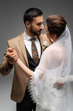Arabian groom dancing with bride in wedding dress isolated on grey stock vector